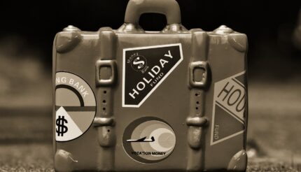 Suitcase with holiday fund stickers packed and ready for your business sell-by date